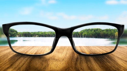 Clear lake in glasses on the background of blurred nature